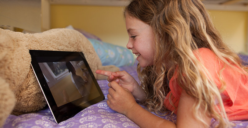 Girl using tablet to watch recorded programming